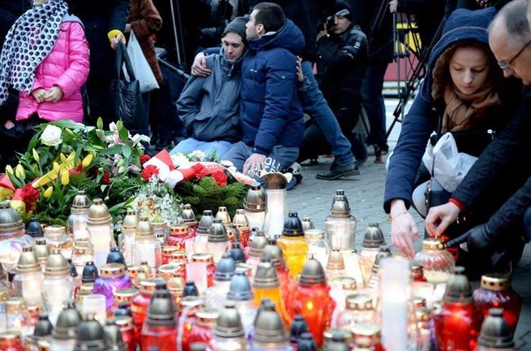 . Warsaw (Poland), 14/11/2015.- People place flowers and light candles in tribute for the victims of the 13 November Paris attacks in front of the French embassy in Warsaw, Poland, 14 November 2015. At least 120 people have been killed in a series of attacks in Paris on 13 November, according to French officials. Eight assailants were killed, seven when they detonated their explosive belts, and one when he was shot by officers, police said. (Varsovia, Polonia, Francia) EFE/EPA/JACEK TURCZYK POLAND OUT