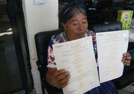 María Quiacaín Culum muestra su acta de defunción, en Sololá. (Foto Prensa Libre: Édgar Sáenz).