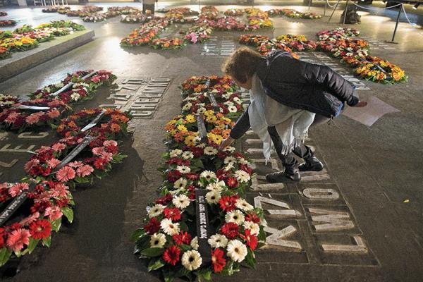 Una familiar de un superviviente del Holocausto deja flores en La Sala del Recuerdo. (Foto Prensa Libre: EFE).