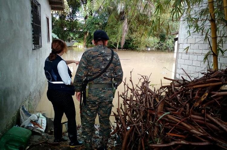 Personas señalan los daños por la crecida de ríos.