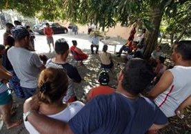 Víctor Berrío (c), informa sobre las novedades migratorias a un grupo de cubanos. (EFE).