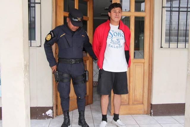 Edwin Geovanni Morales Echeverría es señalado de haber disparado a sus hermanos. El hombre es trasladado a un juzgado por un agente de la PNC. (Foto Prensa Libre: PNC)