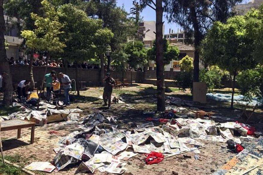 Varios cuerpos cubiertos con papeles de periódicos tras producirse la explosión de un artefacto en un centro cultural en Suruc, (Turquía). (Foto Prensa Libre: EFE).