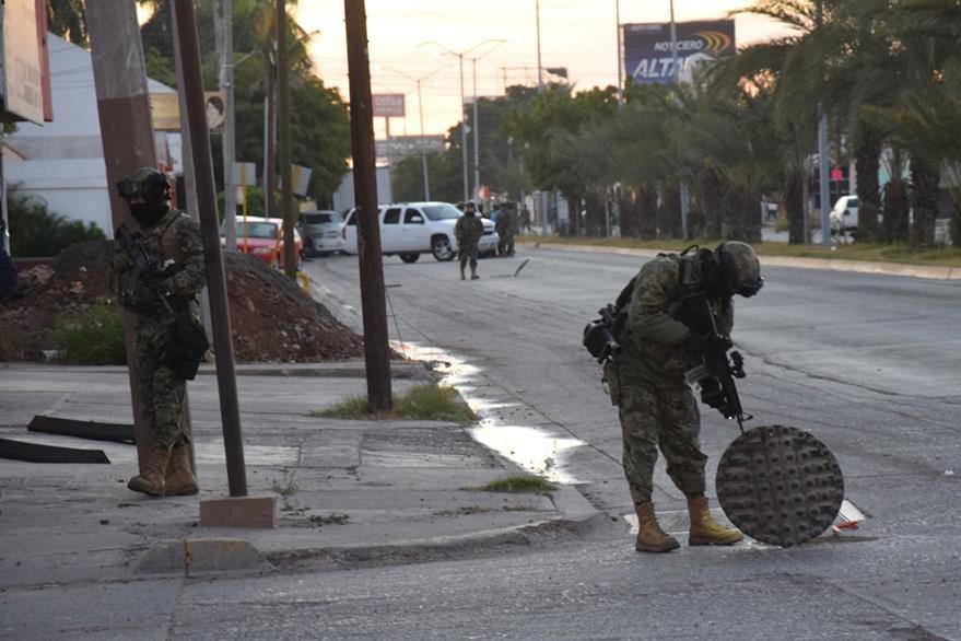 Soldados vigilan sistema de drenajes en una ciudad de Sinaloa, lugar por donde escapó por primera vez. (AP)