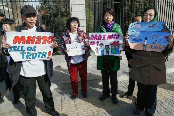 """Manifestantes portan carteles donde piden a la aerolínea que les diga """"la verdad"""" de lo ocurrido con el vuelo MH370. (Foto Prensa Libre: EFE)."""
