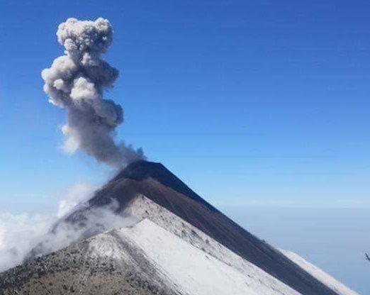 Las fumarolas del Volcán de Fuego salen entre una ladera blanca por la nieve.