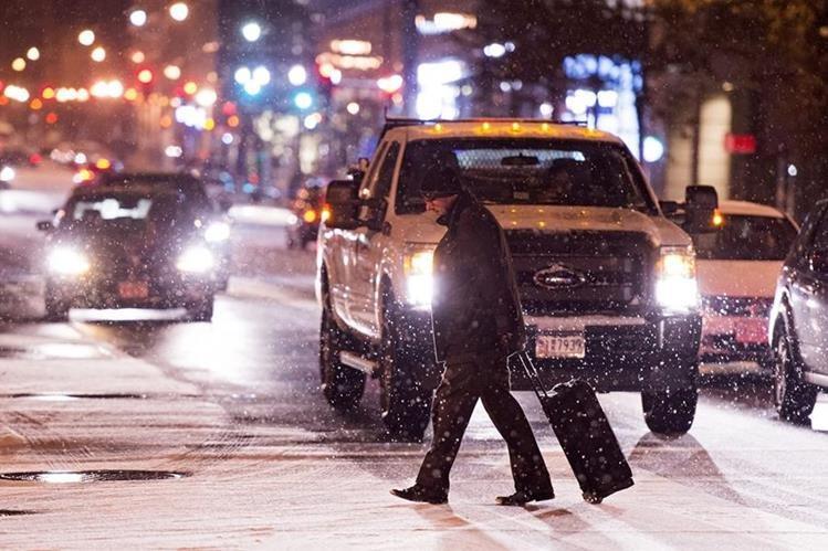 Un hombre cruza una calle nevada en Washington DC. (Foto Prensa Libre: EFE).