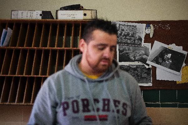 Un preso se pone delante de un tablero con fotografías de varios perros. (AFP).
