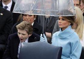 Barron Trump bosteza mientras su madre, Melania Trump, lo protege de la llovizna que cayó durante la ceremonia de toma de posesión. (Foto Prensa Libre: AFP)