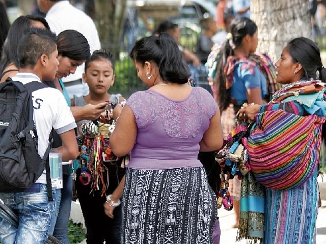 Vendedores ofrecen sus productos a turistas, en el parque de Antigua Guatemala.
