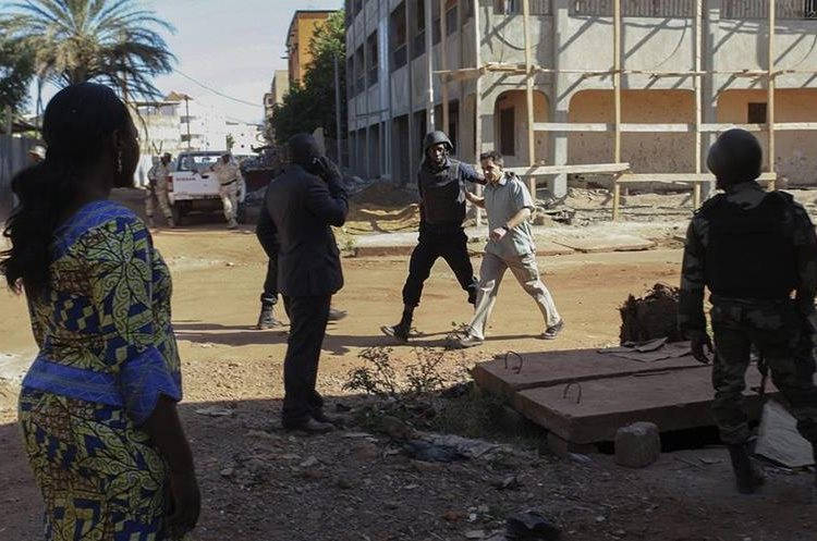 BMK01. BAMAKO (MALI), 20/11/2015.- Un rehén es escoltado por personal militar de Mali a su salida del hotel de lujo Radisson Blu en Bamako, Mali, el 20 de noviembre del 2015. Las fuerzas de seguridad han logrado evacuar a 80 de las 170 personas tomadas como rehenes, en medio de un tiroteo de los hombres armados que atacaron el hotel Radisson de la capital maliense, Bamako, y que han causado al menos tres muertos y varios heridos. EFE/Str