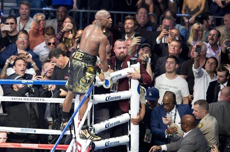 El boxeador estadounidense Floyd Mayweather (c) se sube a las cuerdas del ring para celebrar su triunfo por nocaut técnico.