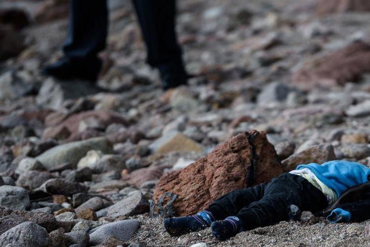 Policías turcos colocan el cuerpo de un niño ahogado en la costa de Canakkale. (Foto Prensa Libre:AFP).