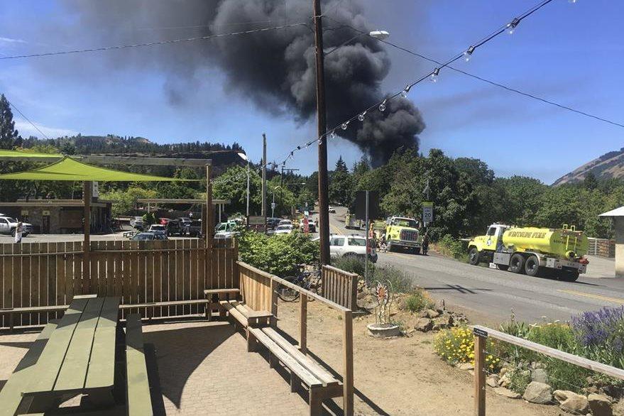 Una espesa nube de humo se eleva en el lugar del descarrilamiento del tren. (Foto Prensa Libre: AP).