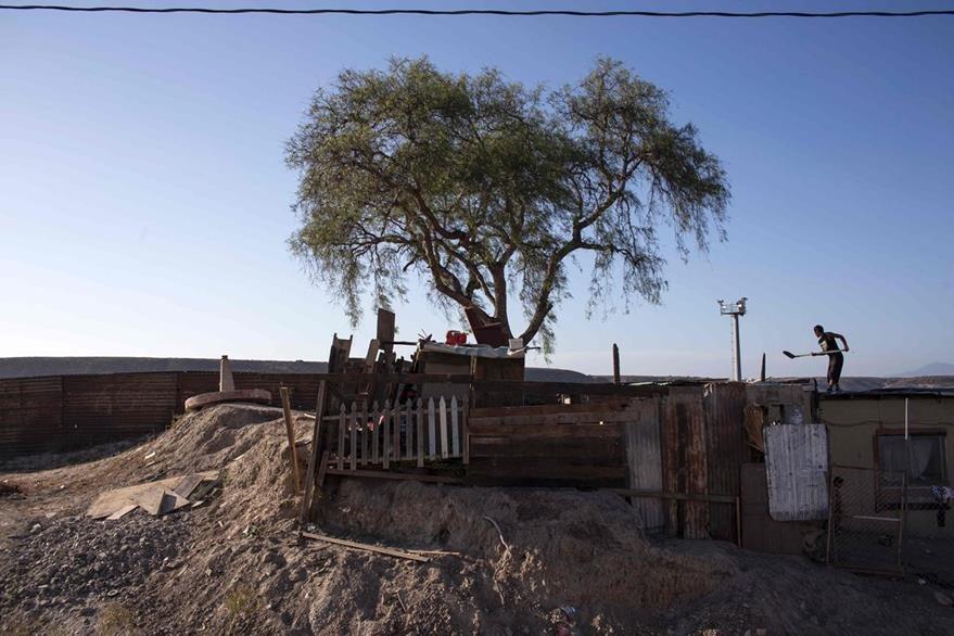Un hombre repara su humilde vivienda en la frontera méxico-estadounidense. (Foto Prensa Libre: AFP).