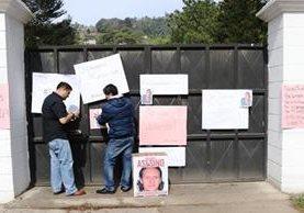Amigos y familiares colocan carteles en la vivienda donde se presume ocurrieron los hechos. (Foto Prensa Libre: María José Longo)