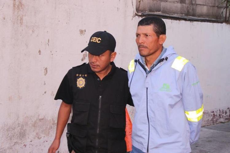 Santos Reyes Palacios es resguardado por un agentes de la Policía Nacional Civil. Es sospechoso de haber asesinado a su esposa. (Foto Prensa Libre: Enrique Paredes)