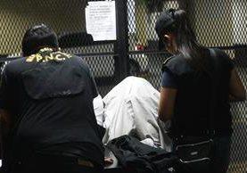 Santos Mejía, con el rostro cubierto, fue detenida, sospechosa de haber solicitado un soborno. (Foto: Álvaro Interiano)