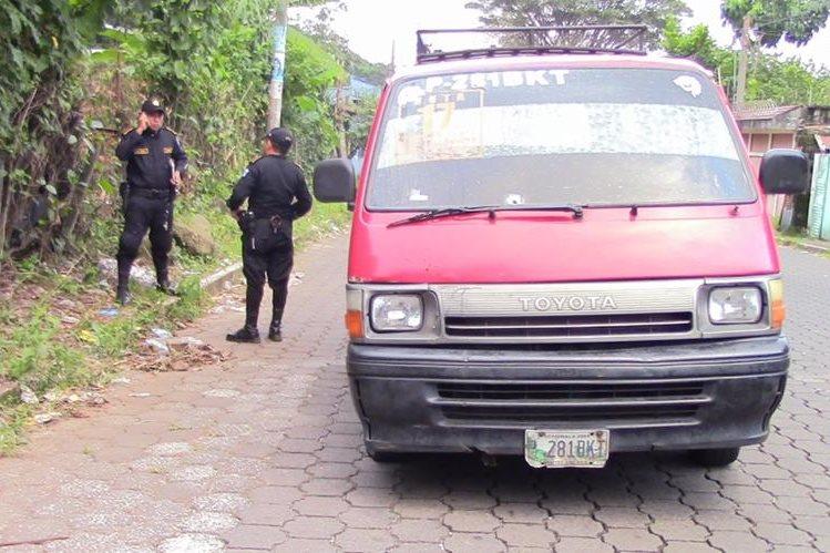 Agentes de la PNC cuidan sitio donde ocurrió el ataque aramdo a microbús, en Mazatenango, Suchitepéquez. (Foto Prensa Libre: Melvin Popá)