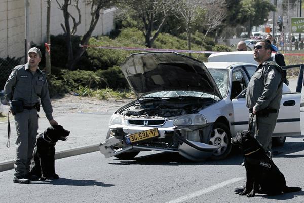 Policías israelíes  cuidan el lugar del  atentado en donde un carro atropelló a varios guardias de seguridad. (Foto Prensa Libre: AFP)