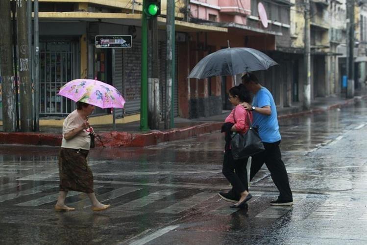 Personas caminan en una calle de la zona 1 durante una tarde de lluvia (Foto Prensa Libre: Hemeroteca PL)
