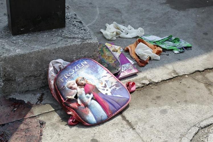 En el lugar quedó la mochila con cuadernos de una de las víctimas. (Foto Prensa Libre: Paulo Raquec)