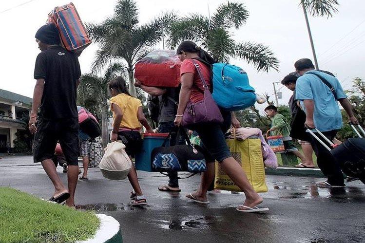 Varias personas abandonan la ciudad de Tabaco, provincia de Albay, Filipinas. (Foto Prensa Libre: EFE).