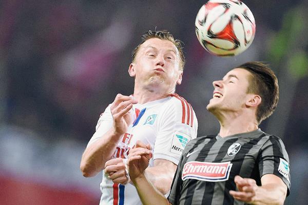 Ivica Olic del Hamburgo —izquierda— y Christian Guenter, durante el juego de ayer en el arranque de la fecha en la Bundesliga. (Foto Prensa Libre: EFE)