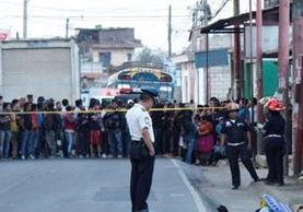 Un oficial de PNC observa el cadáver del ayudante de bus que fue ultimado en Chimaltenango. Al fondo, decenas de curiosos en la escena. (Foto Prensa Libre: Víctor Chamalé)