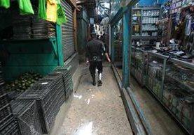 Un investigador de la PNC revisa los comercios cercanos al lugar del incidente, en busca de evidencias. (Foto Prensa Libre: Érick Avila)