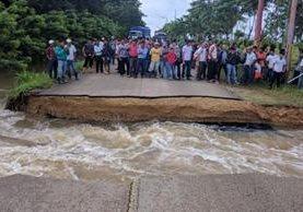 Vecinos observan daño en ruta en comunidad El Tamarindo (Foto Prensa Libre: Rigoberto Escobar).
