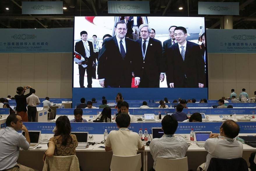 Los periodistas siguen desde la sala de prensa la llegada del presidente del Gobierno español en funciones, Mariano Rajoy (i), al aeropuerto Internacinal de Hangzhou Xiaoshan, para participar en la cumbre del G20. (Foto Prensa Libre: EFE)