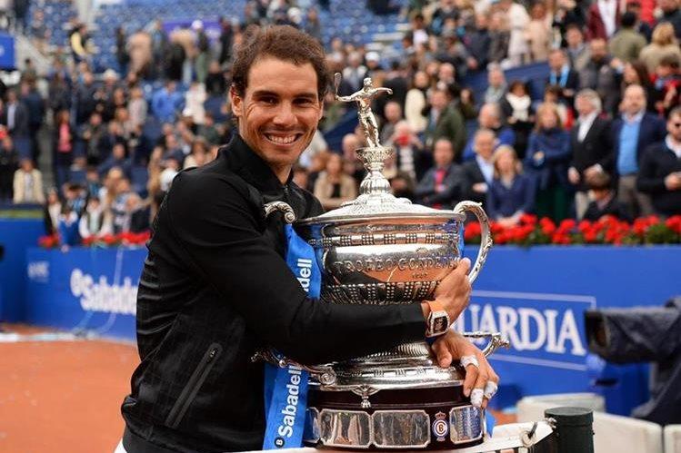 Rafael Nadal abraza su décimo trofeo del abierto de Barcelona. (Foto Prensa Libre: AFP)