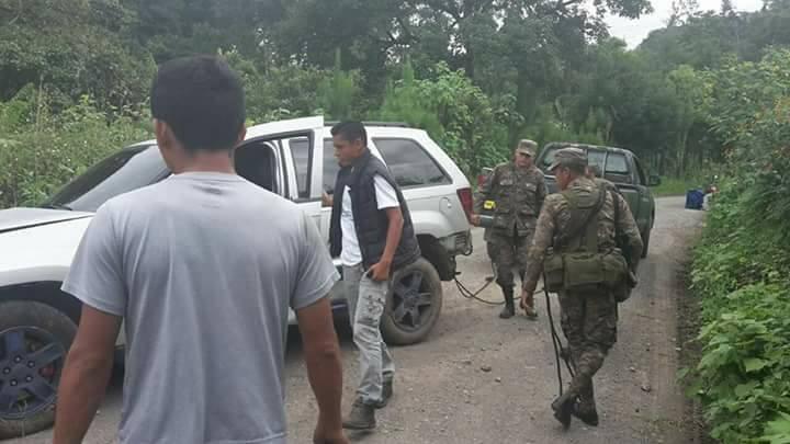 Érick Barrondo observa su vehículo luego de ser auxiliado por elementos del ejército. (Foto Prensa Libre: Twitter Ejército de Guatemala)