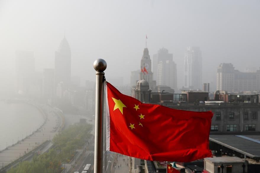 La bandera nacional china se observa en la fotografía. De fondo la ciudad de Shanghai que presenta una exagerada polución. (Foto Prensa Libre: AP).
