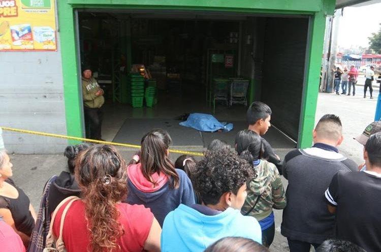 Una de las persona muertas en el ingreso de un supermercado ubicado en la Calzada San Juan, colonia La Florida, zona 19. (Foto Prensa Libre: Cortesía)