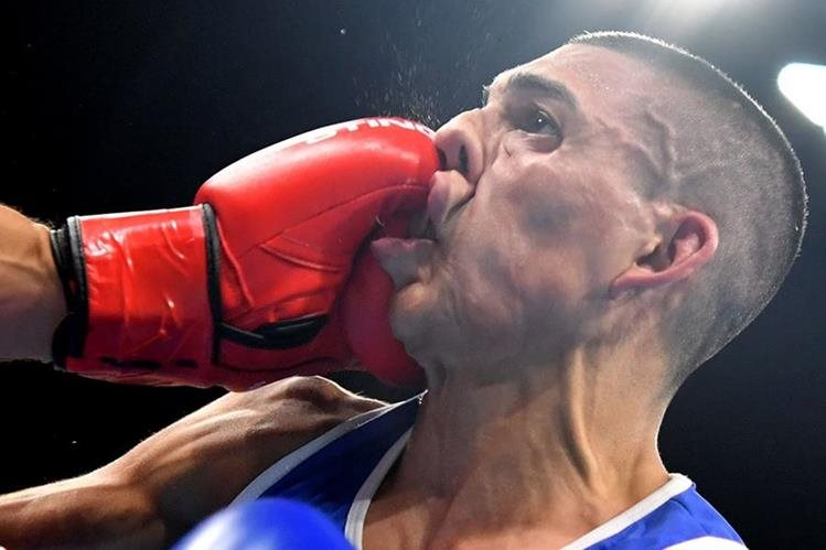Teófimo López recibe un fuerte puñetazo de Sofiane Oumiha durante su debut en Río. (Foto Prensa Libre: AFP)