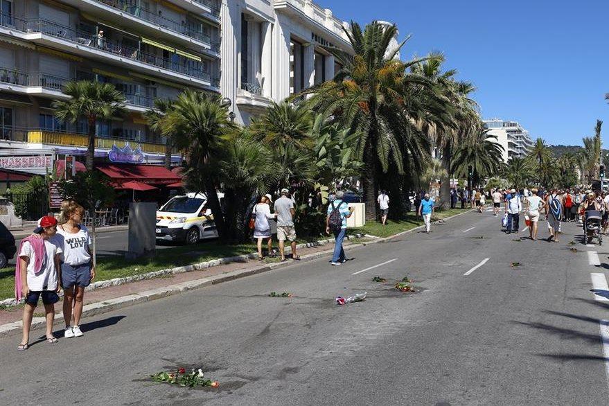Personas caminan en la vía donde ocurrió la tragedia en Niza, y en dnde cientos han dejado flores en memoria de las víctimas. (Foto Prensa Libre: AP).
