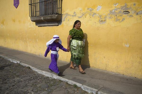 Una mujer indígena acompaña a un pequeño cucurucho. (Foto Prensa Libre: AP)