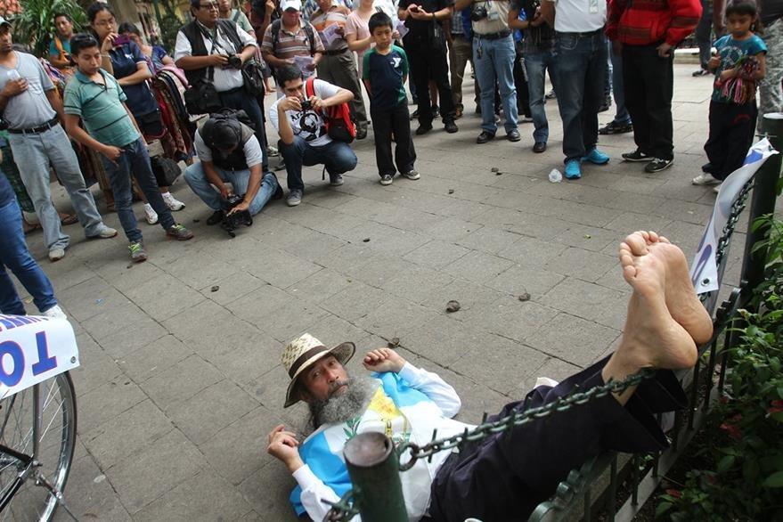 Oswaldo Ochoa, El Caminante, descansa en el parque central de Antigua Guatemala, en donde pernoctará para reiniciar el jueves su travesía en contra de la corrupción hacia la capital. (Foto Prensa Libre: Miguel López)