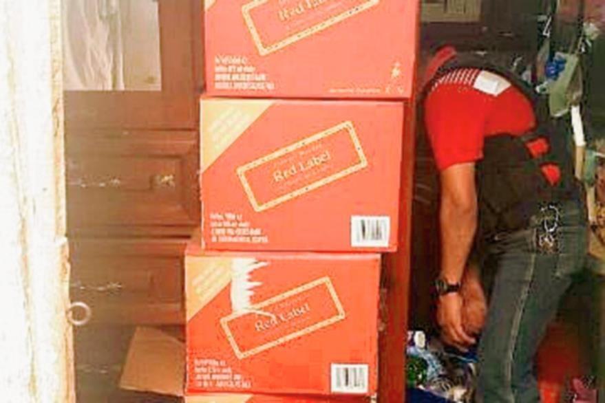 Cajas y botellas de licor fueron localizadas en la residencia del detenido. (Foto Prensa Libre: MP)