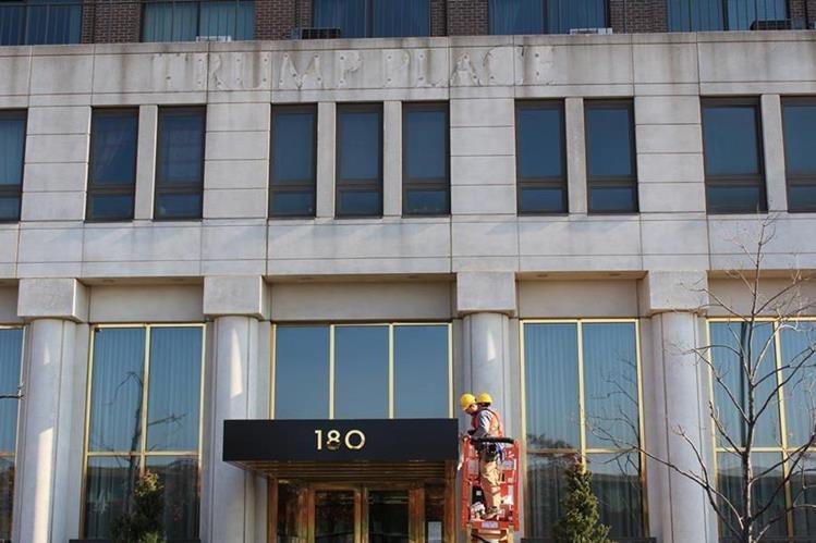 Obreros retiran el letrero Trump Place de la fachada de uno de los tres edificios de alquiler de lujo situados en el barrio de Upper West Side. (Foto Prensa Libre: EFE)