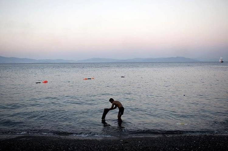 """A migrant washes his clothes on a beach near a police station on the Greek island of Kos, on August 11, 2015. Tensions on the tourist island are high with its mayor claiming there were 7,000 migrants stranded on Kos, which has a population of only 30,000 people. Overwhelmed police beat migrants with truncheons and sprayed them with fire extinguishers as its mayor warned of a """"bloodbath"""" if the crisis gets worse. AFP PHOTO / ANGELOS TZORTZINIS"""