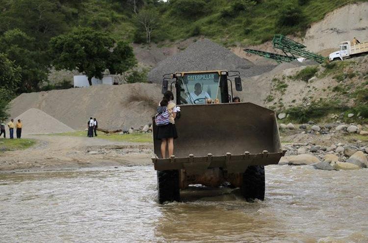 Una estudiante es transportada en una excavadora para cruzar el río Motagua, en Pixcayá, Montúfar, San Juan Sacatepéquez. (Foto Prensa Libre: Oscar Felipe)