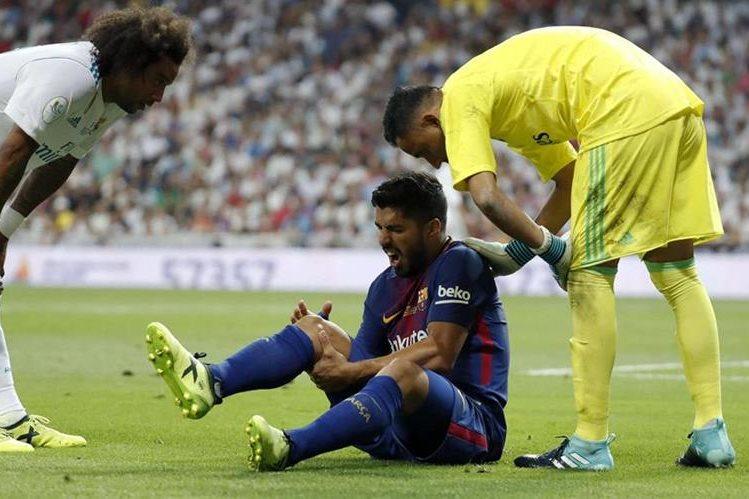 El brasileño Marcelo y el portero Keylor Navas del Real Madrid, consuelan a Luis Suárez quien se queja de la lesión en la rodilla derecha. (Foto Prensa Libre: EFE)