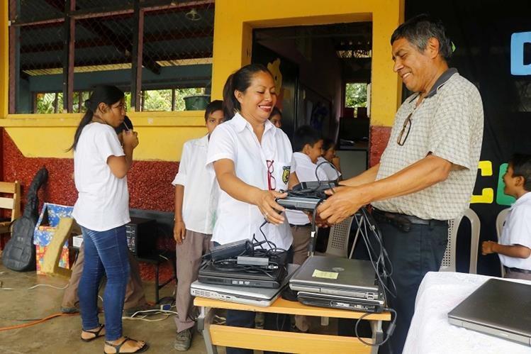 El coordinador de Casa Xelajú, Julio Batres, entrega una computadora a la directora del centro educativo, Silvia Mejía. (Foto Prensa Libre: Rolando Miranda)