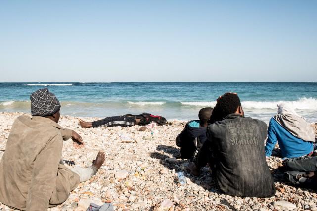 Inmigrantes sobrevivientes del naufragio observa los cuerpos de los ahogados en Harcha, Libia. (Foto Prensa Libre:AFP)
