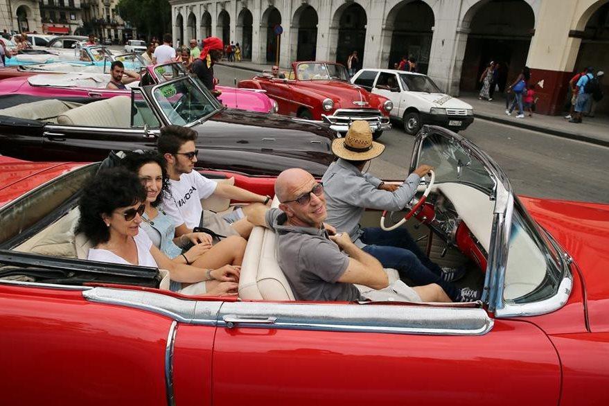 Turistas disfrutan un paseo en un viejo descapotable del pasado siglo en La Habana. (Foto Prensa Libre: EFE).