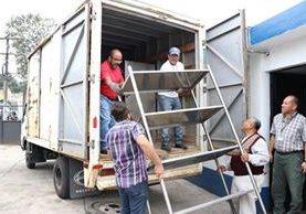 Empleados del Mides cargan mobiliario que se encontraba en el comedor solidario, junto al Hospital Regional de Occidente, en Xelajú. (Foto Prensa Libre: María José Longo)