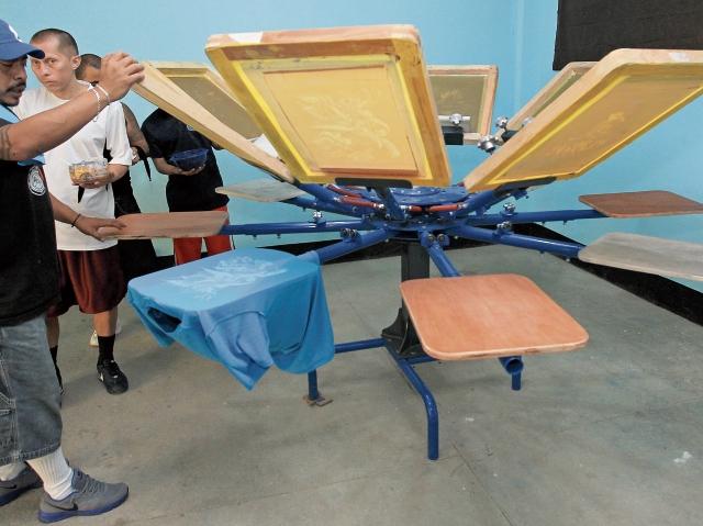 Miembros de la Mara Salvatrucha manipulan una máquina de serigrafía con la que producen las playeras que luego distribuyen a través de intermediarios.
